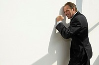 Side profile of a businessman leaning against a wall and looking irritated