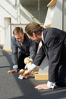 Two businessmen kneeling and playing with stuffed toys