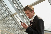 Businessman holding a mobile phone and looking angry