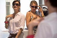 Women trying on sunglasses at a store