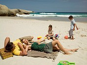 Children playing as their parents relax on a beach