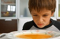 Boy sitting with a bowl of soup