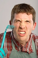 A gardener scratching his cheek with a rake