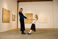 Mother and daughter standing in art gallery