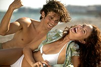 Young Hispanic couple laughing on beach