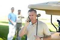 Man talking on cell phone at golf course