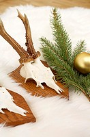 Horns on fur carpet, fir branch and Christmas tree ball