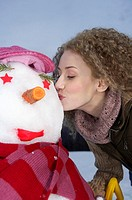 Young woman kissing a snowman, portrait