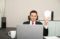 Businessman sitting at desk holding a big light bulb