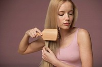 Young blonde woman brushing her hair, close-up
