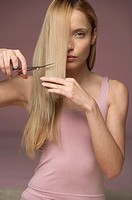 Young blonde woman cutting her hair, close-up