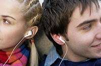 Young couple listening to music about earphones