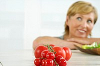 Senior woman looking up, tomatoes in foreground