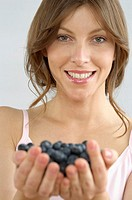 Mid adult woman holding blueberries