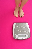 Woman standing next to a weighing scale