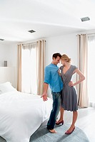 Woman grabbing man in the bedroom