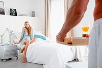 Man bringing breakfast in bed to woman