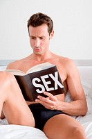 Man looking at book about sex
