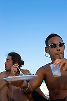 Young men eating at beach party