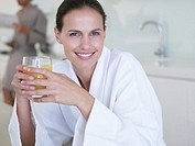 Woman in robe with orange juice and man in background (thumbnail)