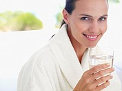 Woman in robe outdoors with glass of water (thumbnail)