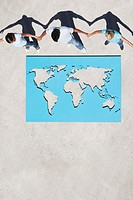 Three people holding hands above world map outdoors