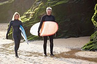 A man and a woman walking down the beach with surfboards