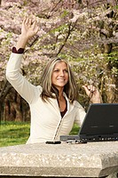 Young woman working in a park waving hello