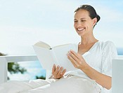 Woman reading and smiling outdoors