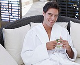 Man in a bathrobe holding a healthy beverage