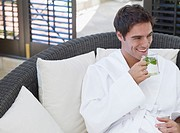 Man in a bathrobe drinking a healthy beverage