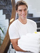 Man holding a pile of towels