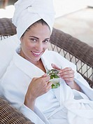 Woman relaxing in a bathrobe holding a health drink