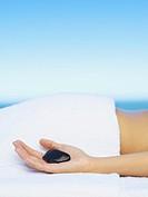 A woman´s hand holding a massage stone