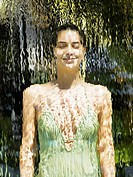 Woman in a bathing suit behind a waterfall