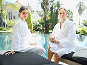 Two women relaxing in bathrobes by a pool