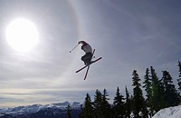 Skier jumping into the sun with skis crossed, Courtenay, B C