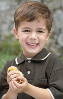 Little boy holding a baby chick on a farm, Waterford, Ontario
