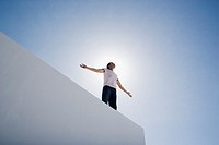 Man standing on wall with arms up and blue sky