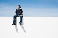 Man sitting on wall smiling outdoors with blue sky (thumbnail)