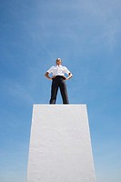 Businesswoman standing on pedestal outdoors (thumbnail)