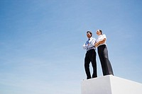 Businessman and woman standing on wall outdoors with blue sky