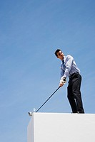 Businessman golfing on roof