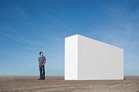 Man standing outdoors looking at white wall