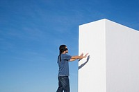 Blindfolded man reaching wall outdoors