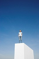 Woman standing on wall outdoors with blue sky