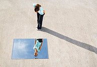 Woman standing above mirror and reflection outdoors (thumbnail)