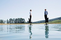 Businesswoman and man standing on office chairs on water
