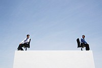 Two businessmen in office chairs on wall outdoors back to back