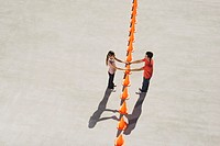 Man and woman holding hands over row of traffic cones